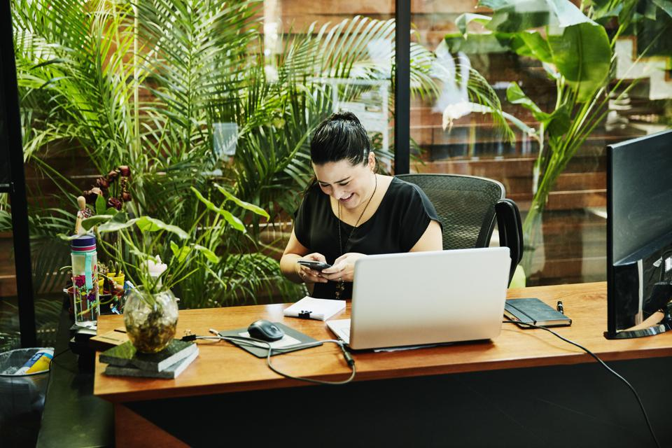 Smiling businesswoman sending message on smart phone while working on office
