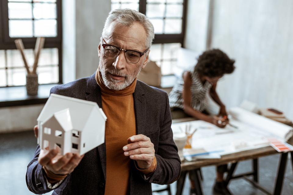 Брадати дизајнер ентеријера са сивом косом држи бели модел куће