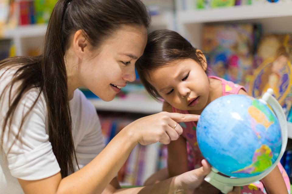 A teacher and a preschool student learning geography on a world globe