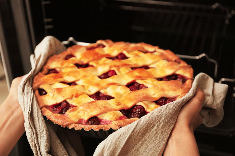 Woman taking freshly baked cherry pie out of oven, closeup