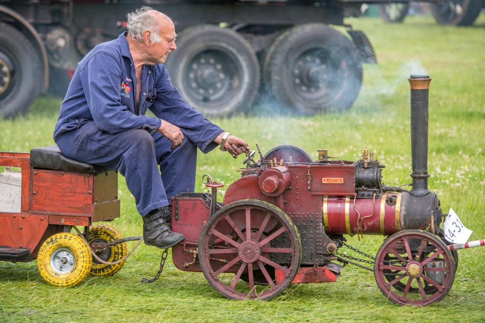 Mature male in blue jumpsuit rides along on miniature tractor steam engine on grass.
