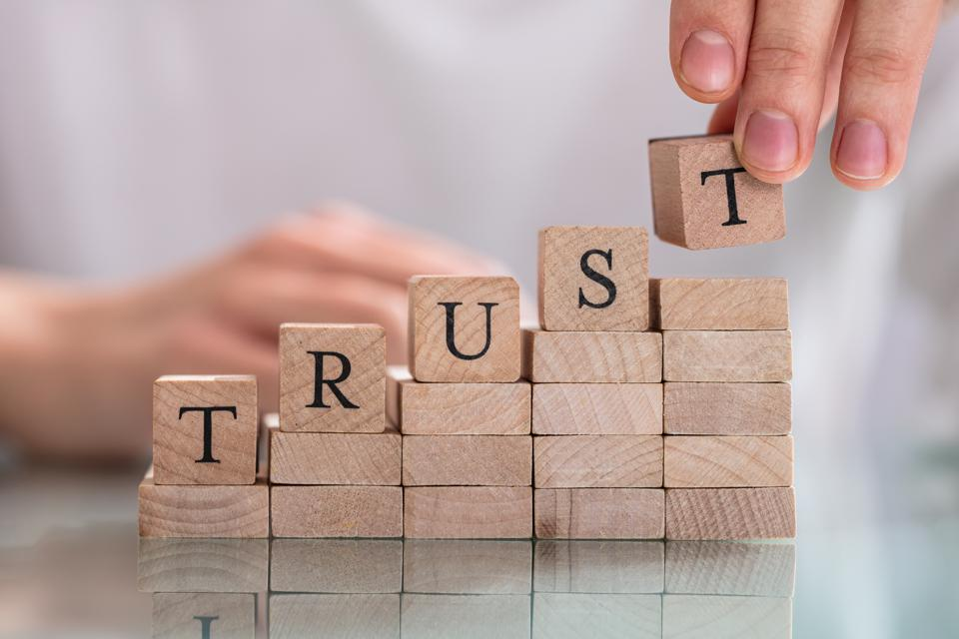 Woman's Hand Placing Last Alphabet Of Word Trust