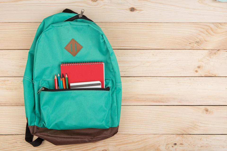 blue backpack, red notebooks and pencils on wooden table