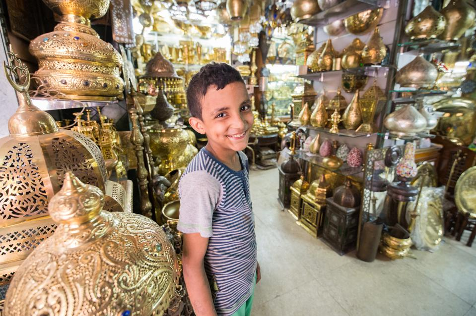 Young Egyptian boy standing in a shop selling ornate gold pots and vases in the outdoor bazaar.