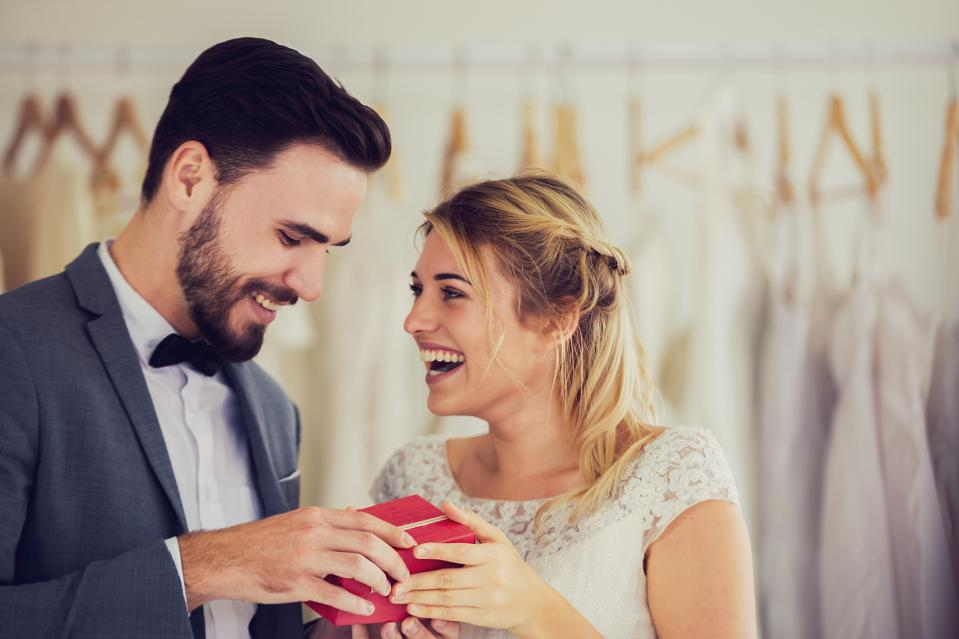 Happy Young Couple Holding Gift While Standing At Bridal Shop