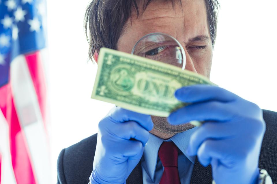 American secret service agent analyzing suspicious counterfeit dollar bill