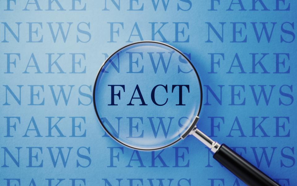 Fake News And Fact Concept - Magnifier And Fake News Text On Blue Background