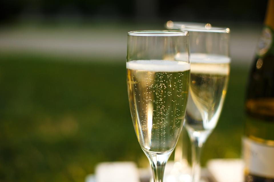 Glasses with champagne on green blurred background. Outdoors picnic weekends