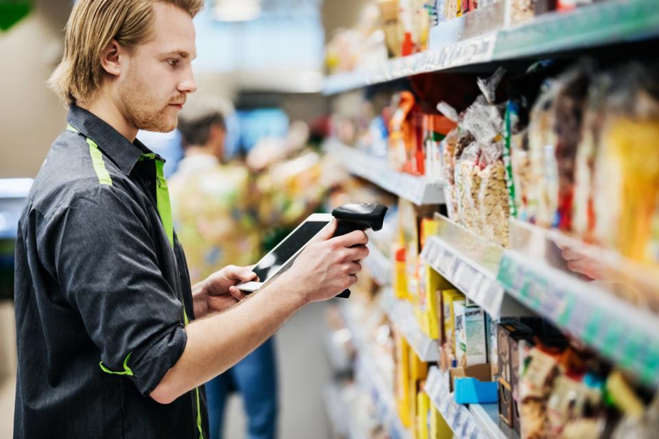 Supermarket Employee Scanning Food Items