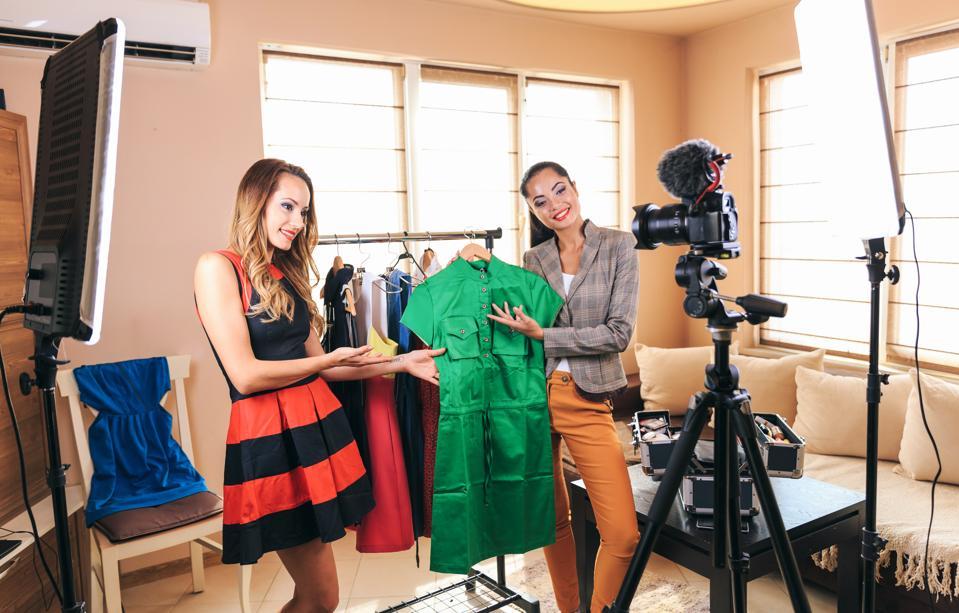 Female fashion vloggers showcasing a new dress.