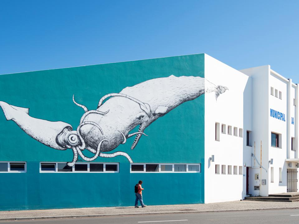 Painting of a sperm whale and giant squid on a wall.