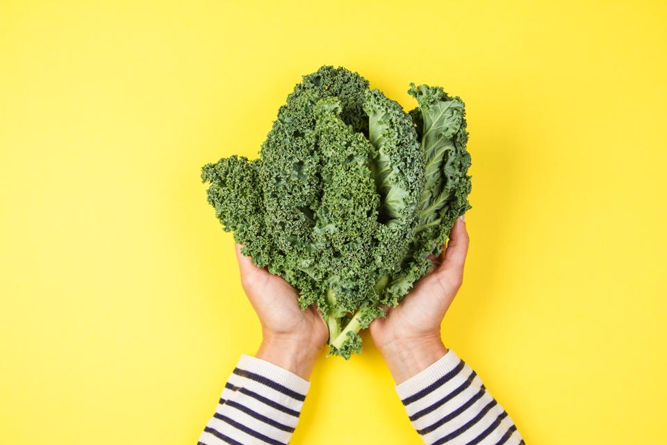 Cropped Image Of Woman Holding Kale Against Yellow Background