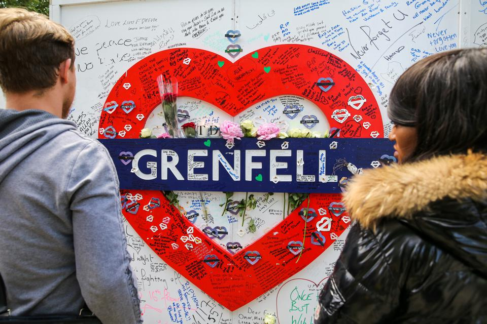 People seen looking at a Grenfell placard. On 14 June 2017,...
