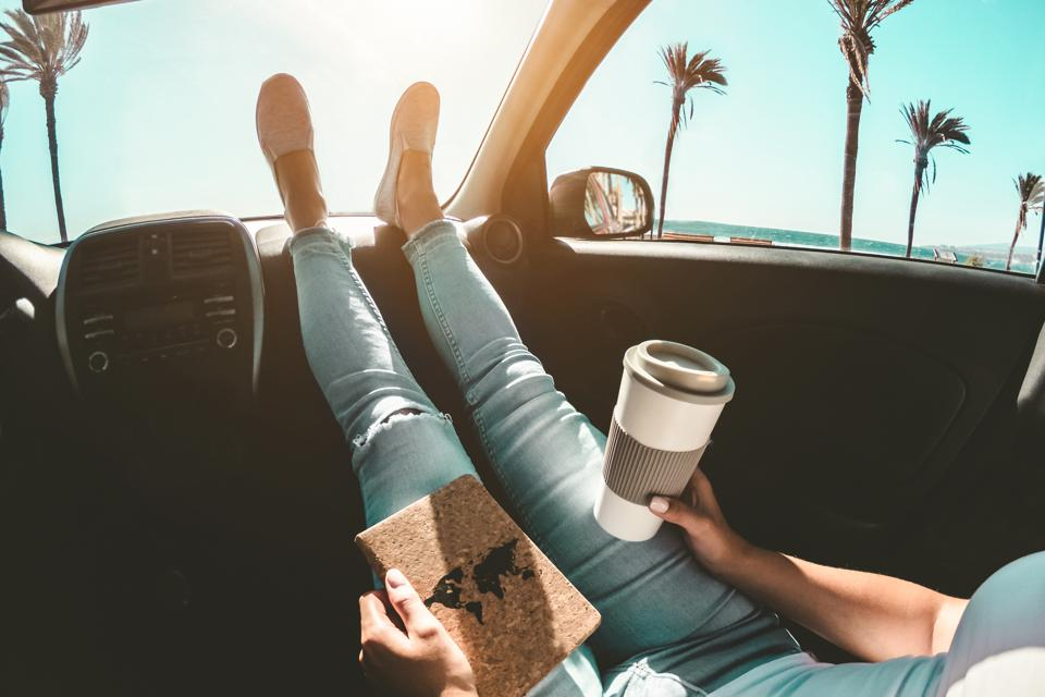 Woman drinking paper coffee cup inside the car with feet on dashboard - girl reading in road trip reading travel book with ocean beach and palm trees in background - travel concept - focus on hands