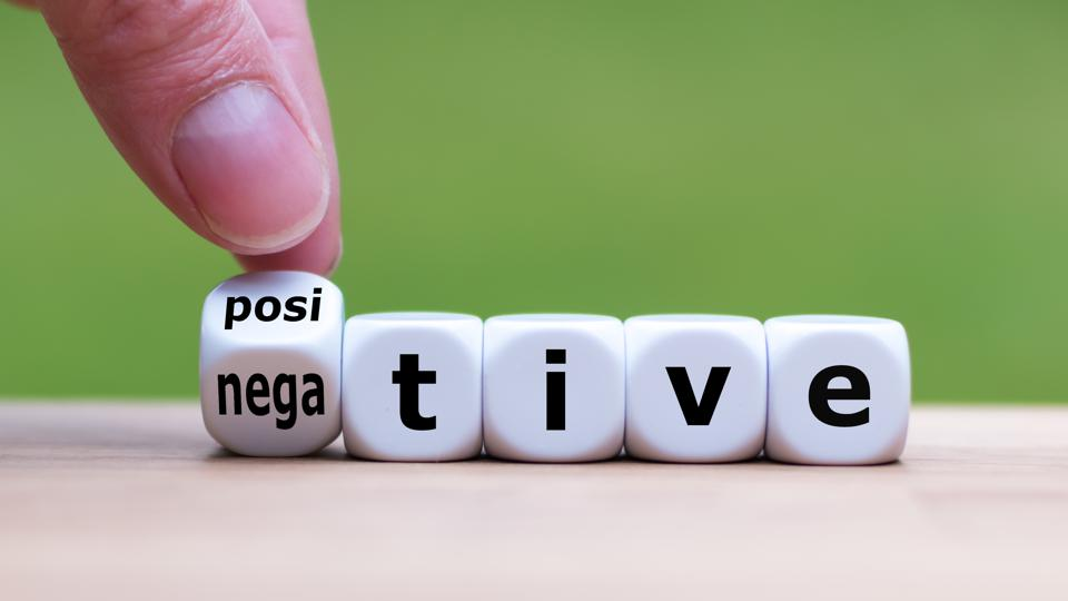 Hand turns a dice and changes the expression ″negative″ to ″positive″.