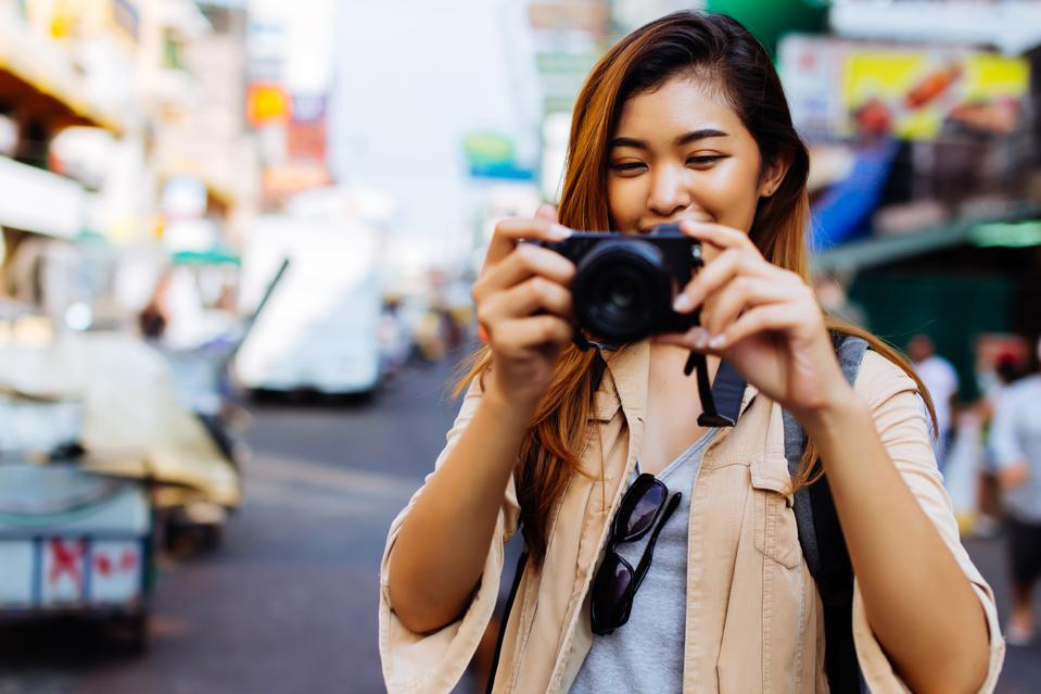 Young woman holding a camera and taking photos in Thailand