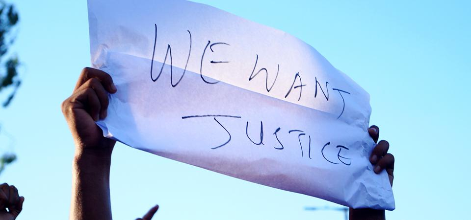 Low Angle View Of Person Holding Paper With Justice Text Against Sky