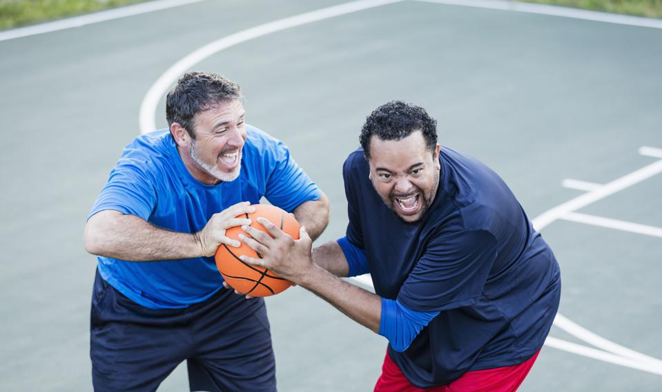 Mature men having fun playing basketball