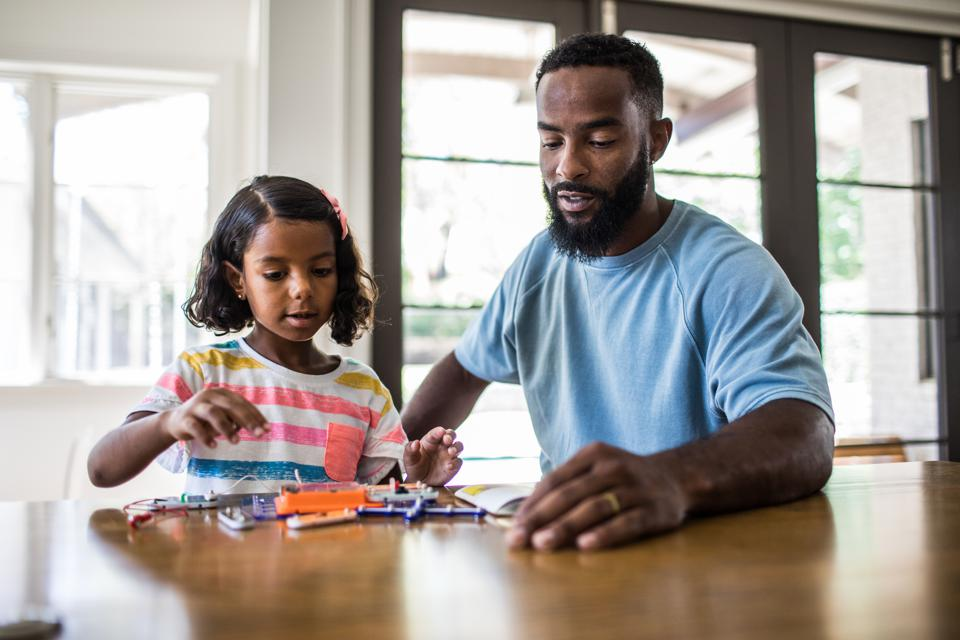 father and daughter working on science project at home