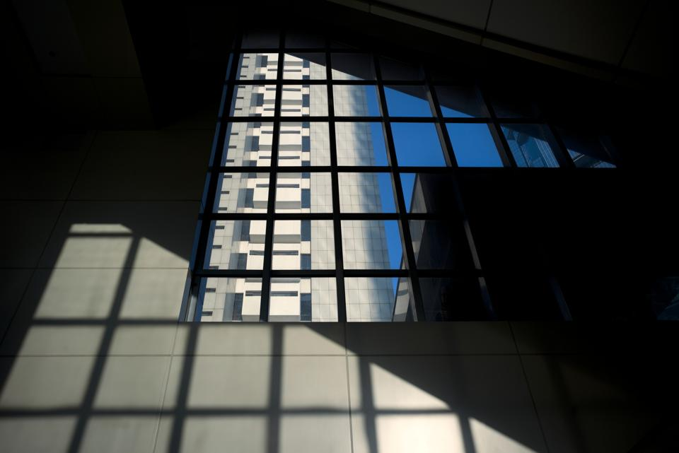 Architectural abstract of large window, building, sky and shadow