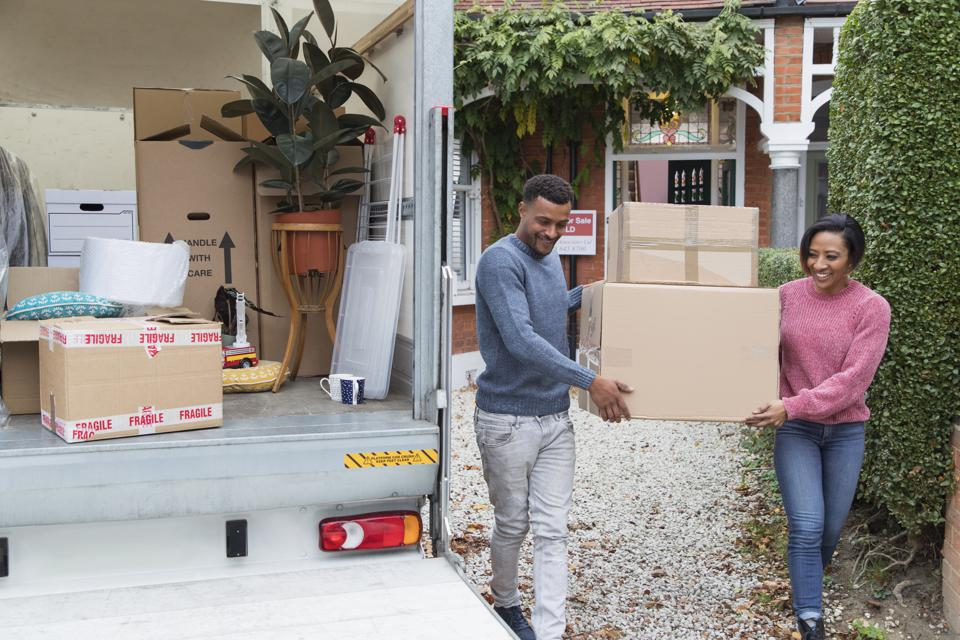 Couple moving out of house, carrying boxes to moving van
