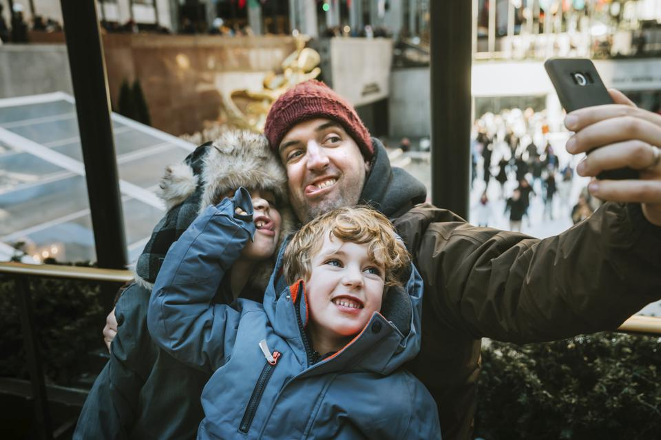 Happy father with sons making face while taking selfie against window in city