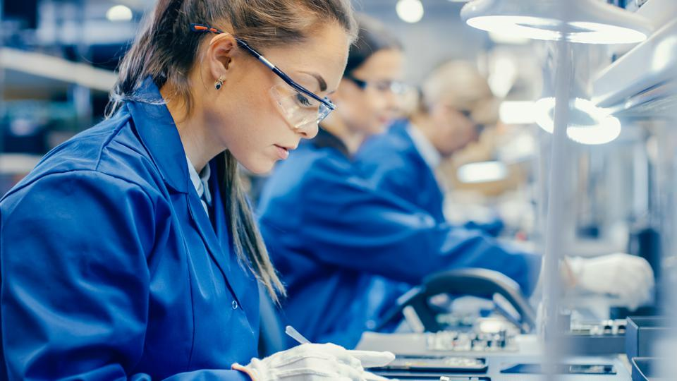Female Electronics Factory Workers in Blue Work Coat and Protective Glasses Assembling Printed Circuit Boards for Smartphones with Tweezers. High Tech Factory with more Employees in the Background.
