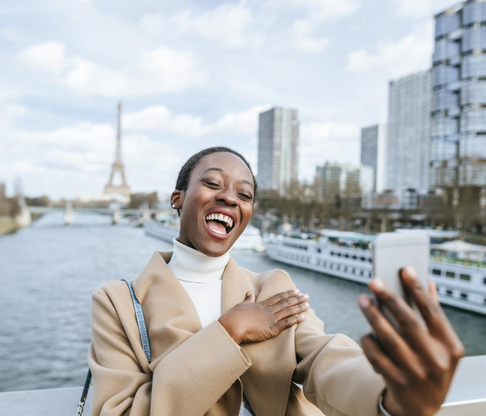 Woman traveler taking a selfie with smartphone with the Eiffel tower in the background