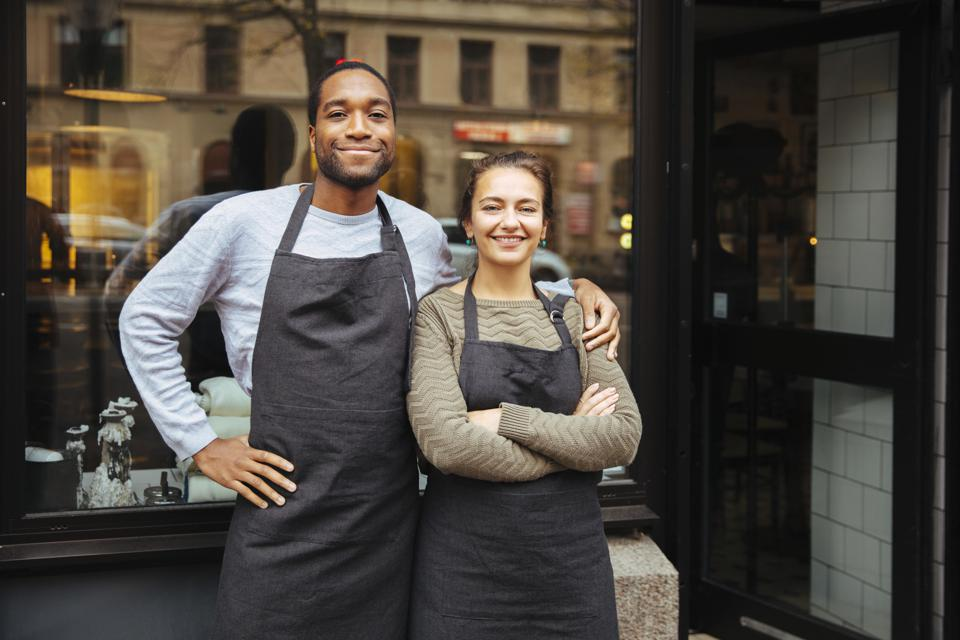 Portrait of confident young owners standing against delicatessen window in city