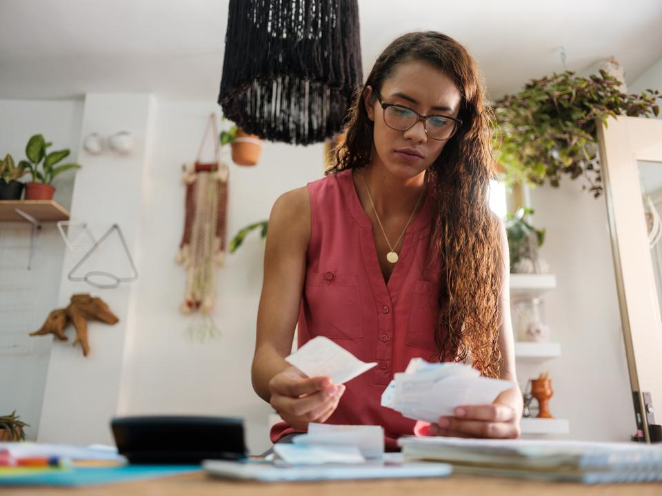 Young latin woman holding receipts and looking at them.