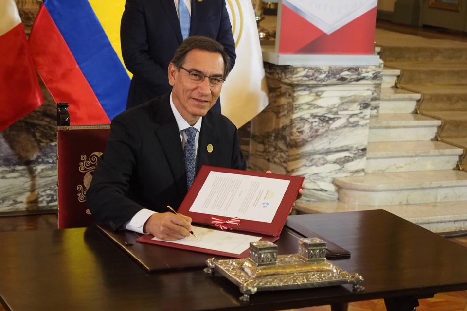 Martin Vizcarra, President of Peru, signing an agreement as...