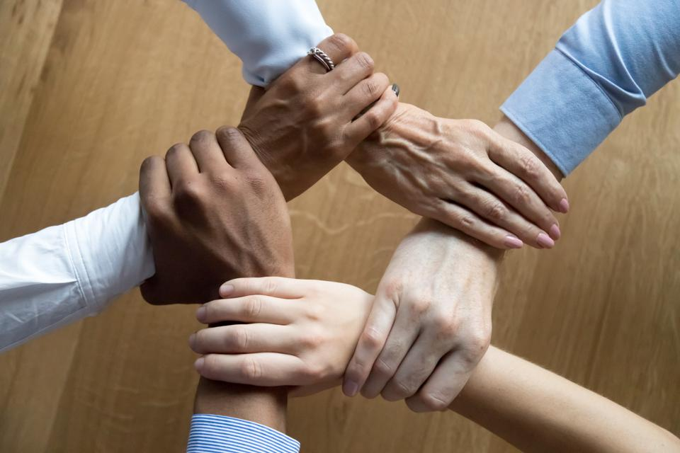Diverse business people team grasping hands, close up top view