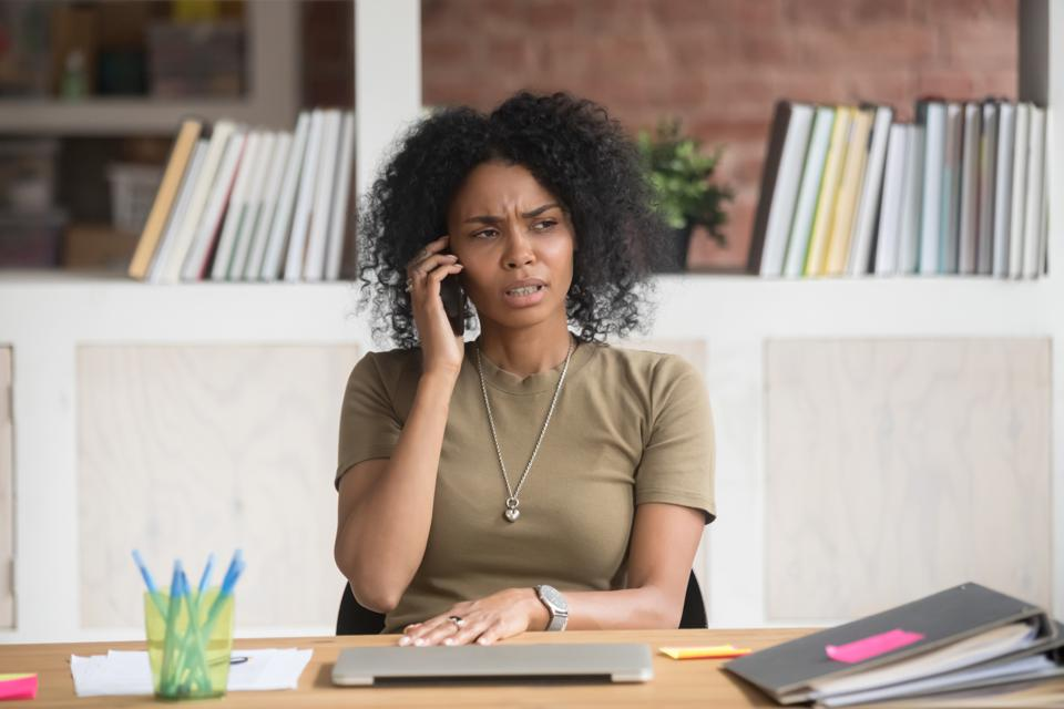 Woman on phone call with anxious facial expression