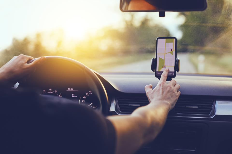 Driver using GPS navigation in mobile phone while driving car