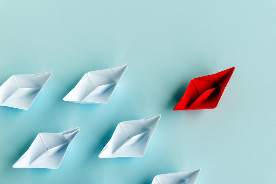 Leadership Concept - Red Paper Boat Followed by White Paper Boat on Blue Background