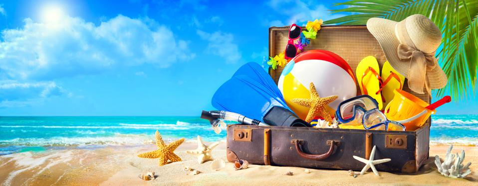 Beach accessories in suitcase on sand.