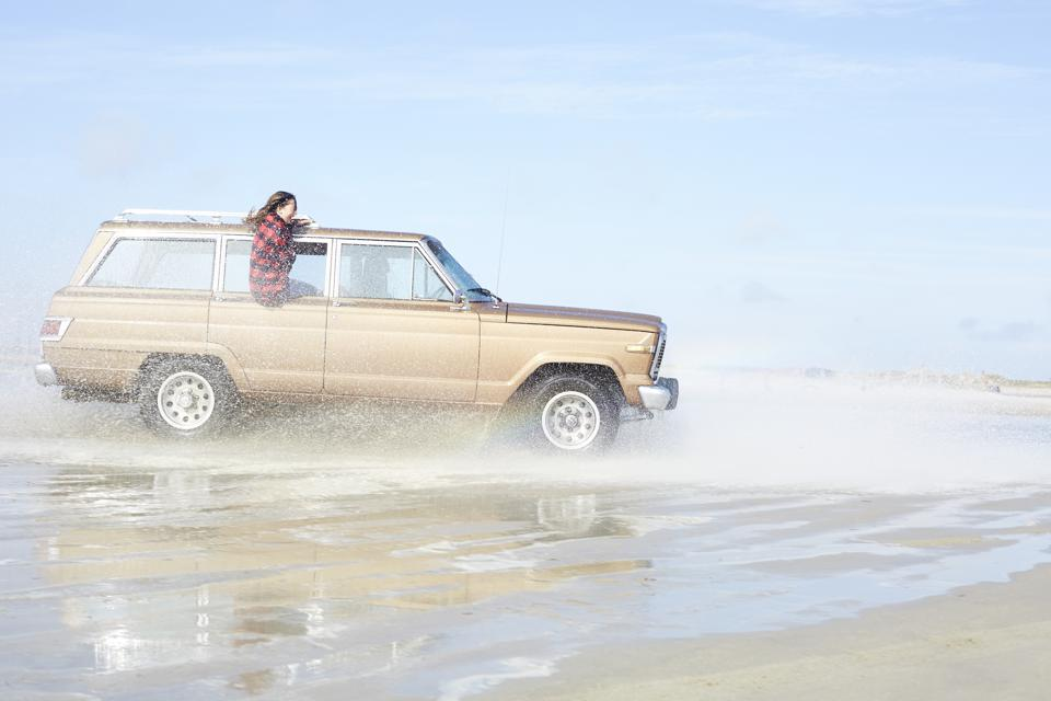 Germany, St Peter-Ording, girl leaning out of window of off-road vehicle driving through water on the beach