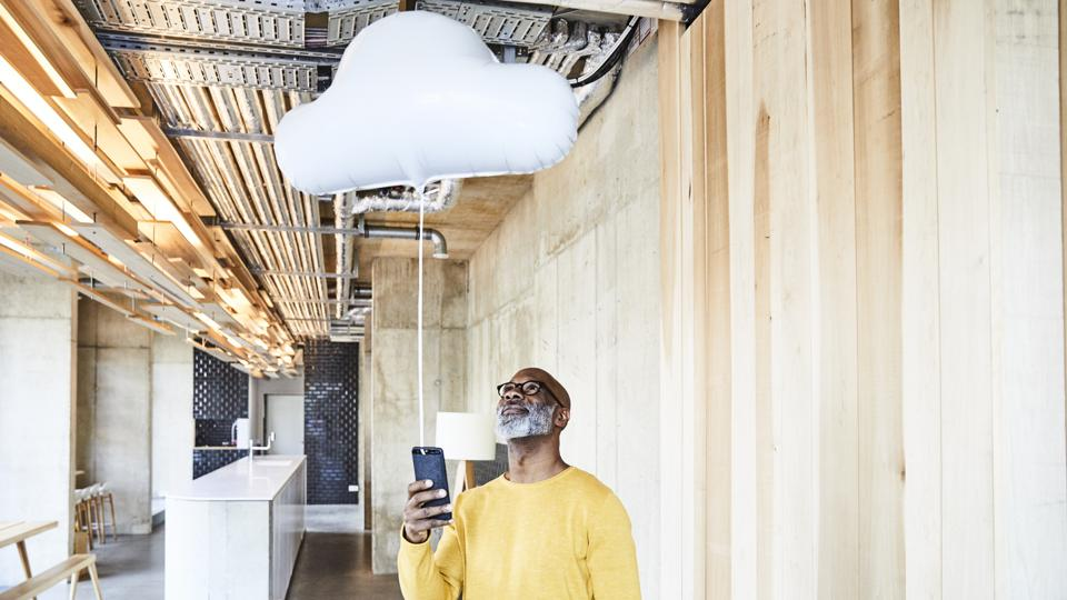 Mature businessman holding cell phone attached to cloud balloon