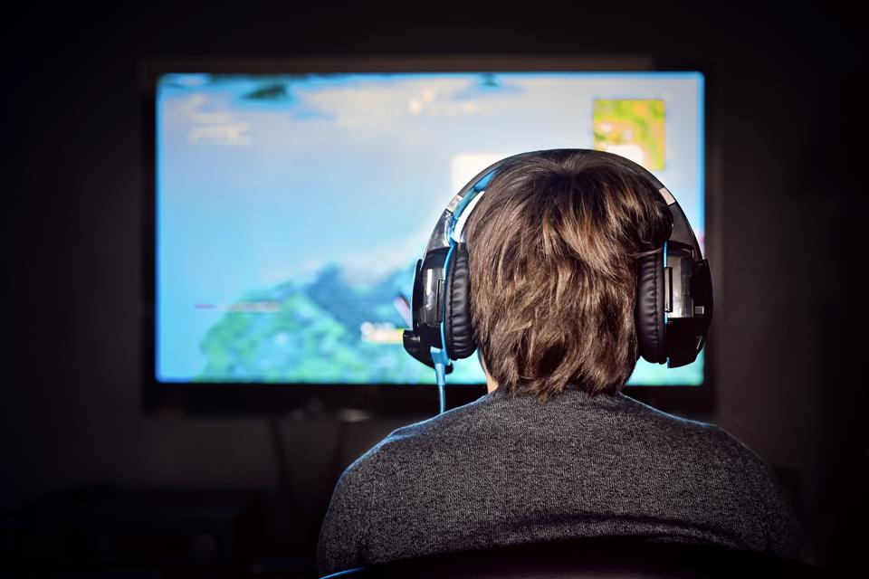 Caucasian gamer wearing a headset plays video game.