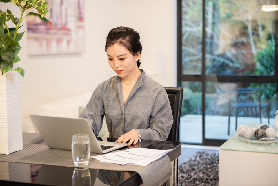 A young Asian woman is using laptop
