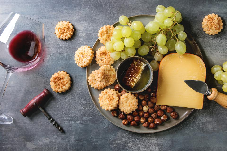 Wine snack. Cheese, grapes, nuts, cheese crackers cookies, honeycombs with laying glass of red wine and knife over dark texture background. Flat lay, space