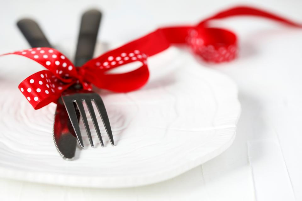Fork and knife tied with a red ribbon on white background with copy space. Food. restaurant and table setting theme - Image