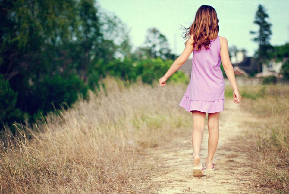 Girl walking along dirt path