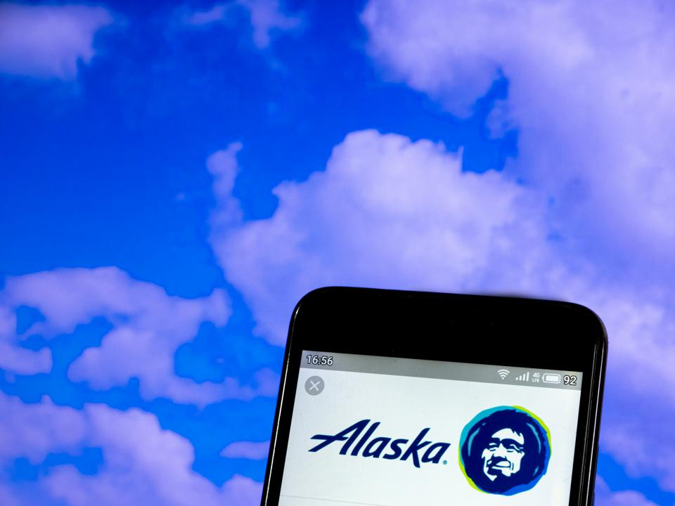 In this photo illustration a Alaska Airlines logo seen...