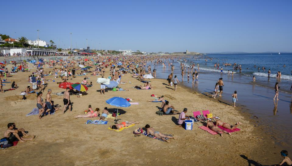 Beachgoers crowd Carcavelos beach on a hot Sunday afternoon
