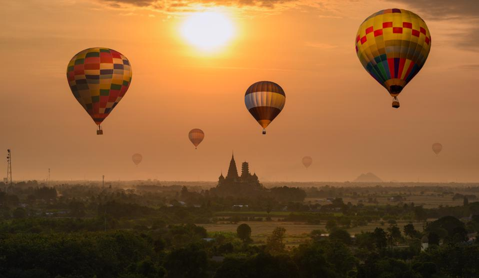 Colorful hot air balloons flying on Wat Tham Sua temple building on hill in sunrise morning