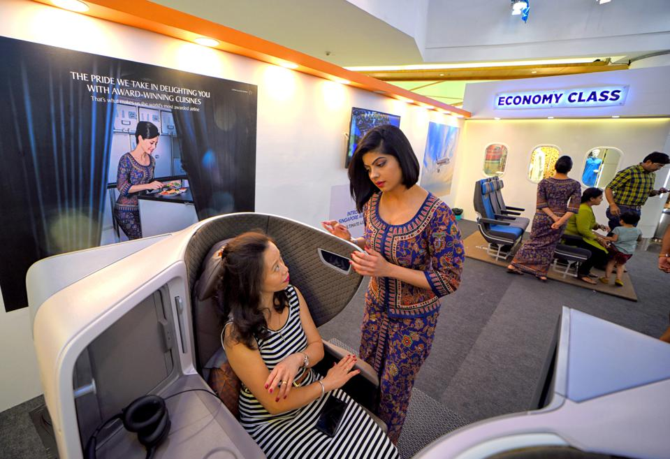 Cabin Crew member of Singapore Airlines gives a...