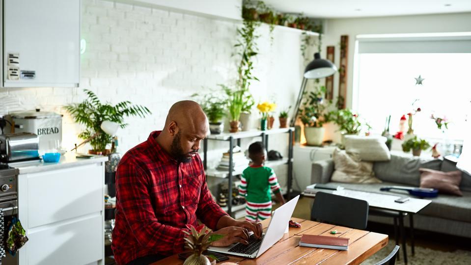 Padre trabajando desde casa en la computadora portátil y cuidando a su hijo