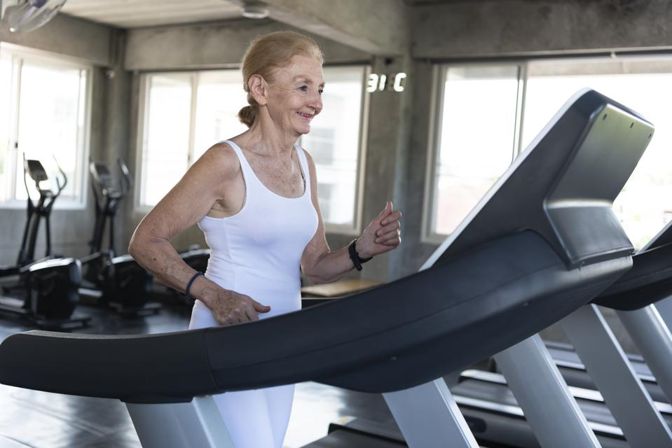 Senior women exercise jogging at gym fitness smiling and happy. elderly healthy lifestyle.