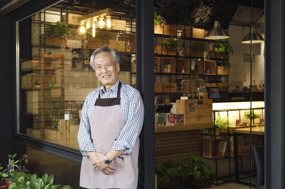 Cafe owner standing outside of his shop